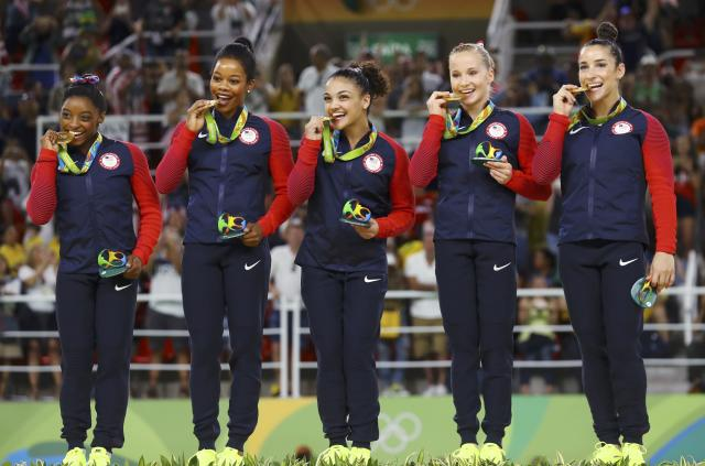 2016 Rio Olympics - Artistic Gymnastics - Final - Women's Team Final - Rio Olympic Arena - Rio de Janeiro, Brazil - 09/08/2016. Simone Biles (USA) of USA, Gabrielle Douglas (USA) of USA (Gabby Douglas), Laurie Hernandez (USA) of USA, Madison Kocian (USA) of USA, Alexandra Raisman (USA) of USA (Aly Raisman) bite their gold medals on the podium after winning the women's team final. REUTERS/Mike Blake FOR EDITORIAL USE ONLY. NOT FOR SALE FOR MARKETING OR ADVERTISING CAMPAIGNS.