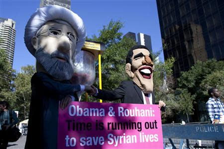 Members of international advocacy group Avaaz take part in protest wearing masks of Iran's new President Rouhani and U.S. president Obama, outside U.N. headquarters in New York