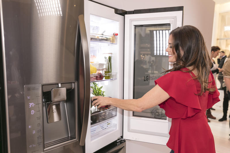 """Celebrity nutritionist Keri Glassman arranges her """"Healthy Shelfie"""" at an LG InstaView Refrigerator event on March 7, 2017 in New York, by knocking twice to light up the LG InstaView fridge's glass panel. Glassman shows how simple organization tips, like keeping healthy food options front and center, can help you achieve a healthier lifestyle."""
