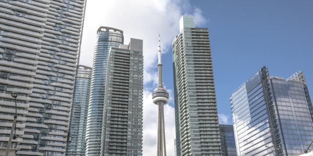 The CN Tower peaks out from behind condos along Toronto's lake shore. Prices for new condos in the city have soared even as sales have dropped by nearly two-thirds.
