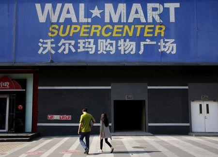 Pedestrians walk past a signboard of Wal-Mart at its branch store in Beijing, China
