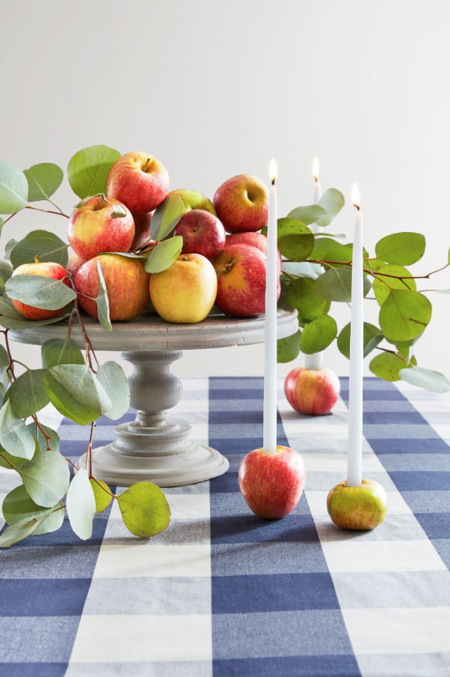 """<p>Odds are you're making <a href=""""https://www.countryliving.com/food-drinks/g973/best-apple-pie-recipe/"""">your famous apple pie</a> this year—which means you'll likely have a few apples left over.  Let them live on as candleholders with this fun, innovative DIY. </p><p><strong>Make the Candleholders:</strong> Use a paring knife to cut a 1-inch deep hole in the top of a few apples, slightly narrower than the candles, and wedge the candles in. Display alone or with stacked apples and seeded eucalyptus on a neutral cake stand.<a href=""""https://www.amazon.com/BOLSIUS-White-Taper-Candles-Avail/dp/B01F49FITE"""" target=""""_blank""""></a></p><p><a class=""""body-btn-link"""" href=""""https://www.amazon.com/BOLSIUS-White-Taper-Candles-Avail/dp/B01F49FITE?tag=syn-yahoo-20&ascsubtag=%5Bartid%7C10050.g.2063%5Bsrc%7Cyahoo-us"""" target=""""_blank"""">SHOP TAPER CANDLES</a></p>"""