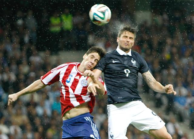 French soccer team forward Olivier Giroud, right, Paraguayan soccer team defender Danilo Fabian Ortiz Soto, challenges for the ball with during the friendly soccer match between France and Paraguay at the Allianz Riviera Stadium, in Nice, southeastern France, Sunday, June 1, 2014. France is preparing for the upcoming soccer World Cup in Brazil starting on 12 June. (AP Photo/Claude Paris)