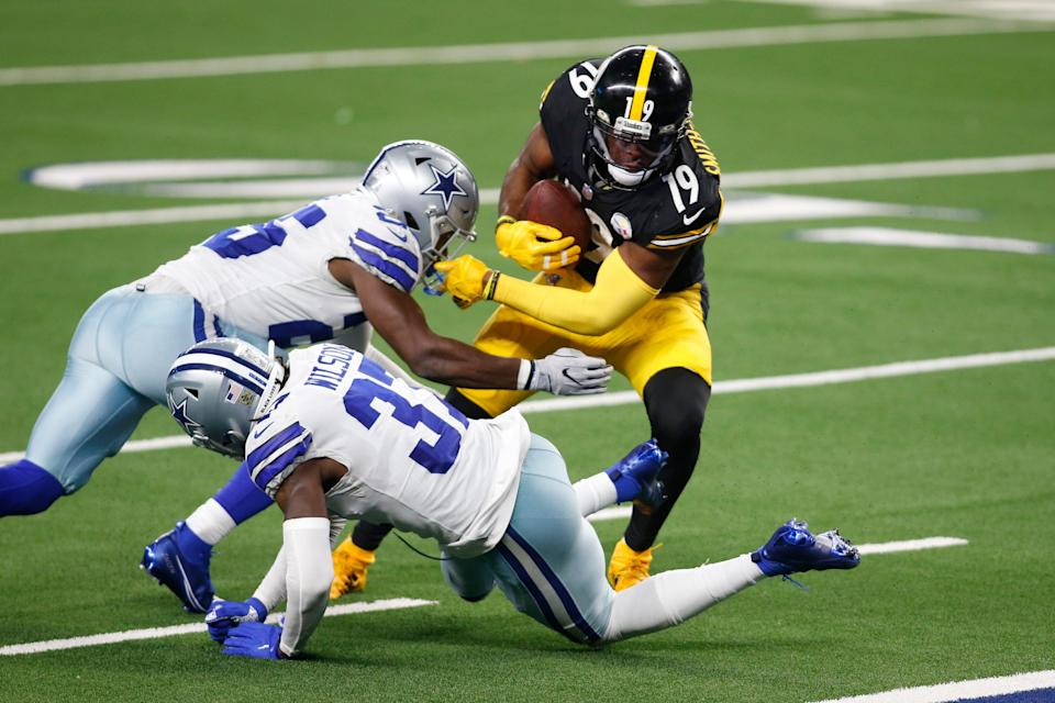 Pittsburgh Steelers wide receiver JuJu Smith-Schuster (19) catches a pass and runs for a touchdown against Dallas Cowboys free safety Xavier Woods (25) and safety Donovan Wilson (37) in the fourth quarter at AT&T Stadium.