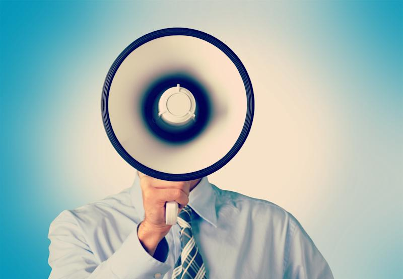 A bullhorn blocks a man's head from our view as he holds it to his mouth.