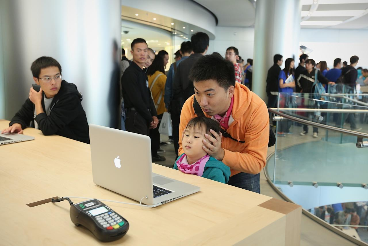 BEIJING, CHINA - OCTOBER 20:  Chinese customers look at the MacBook Pro in the newly opened Apple Store in Wangfujing shopping district on October 20, 2012 in Beijing, China. Apple Inc. opened its sixth retail store on the Chinese mainland Saturday. The new Wangfujing store is Apple's largest retail store in Asia.  (Photo by Feng Li/Getty Images)