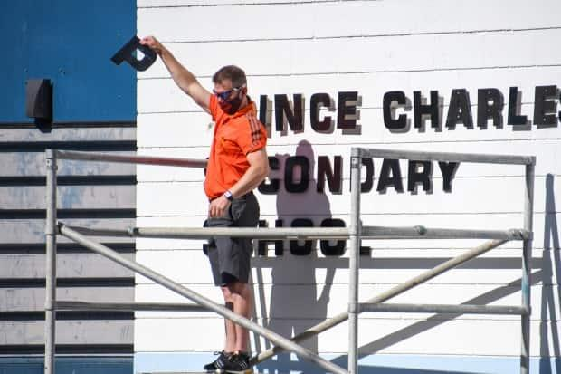 Vice-principal Mike Nelson of Creston Valley Secondary School in Creston, B.C., removes the first letter of Prince Charles's name from the school's exterior signage at a ceremony last Friday. (Jeff Banman - image credit)