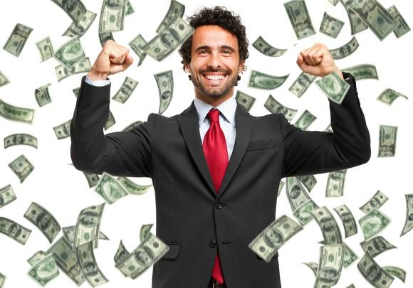 Cash raining down on a very happy man in a suit.