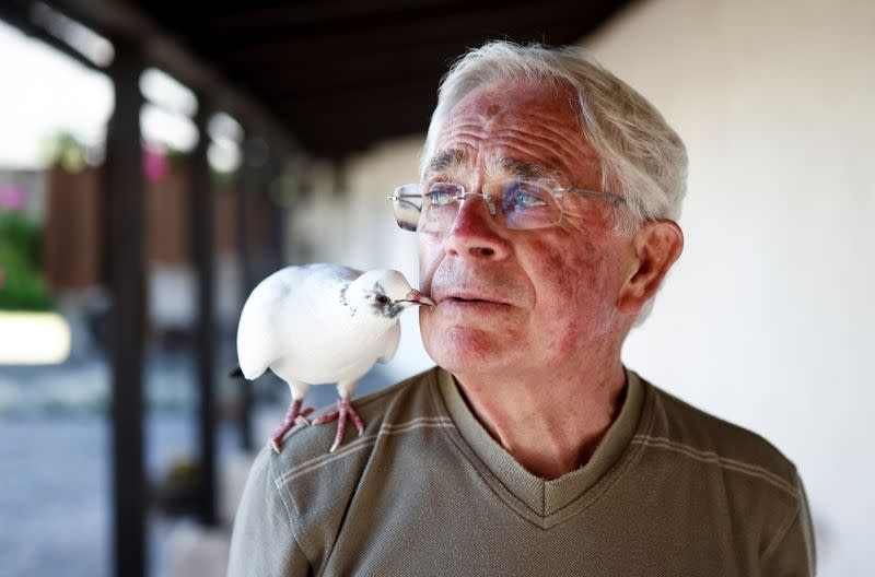 Xavier Bouget, who built a strong relation with a wild pigeon, poses at his garden in Gommenec'h