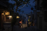 A man walks in the Plaka district of Athens past closed coffee shop and restaurants during a lockdown order by the Greek government to to avoid the spread of the coronavirus in Athens, on Tuesday, April 14, 2020. (AP Photo/Petros Giannakouris)
