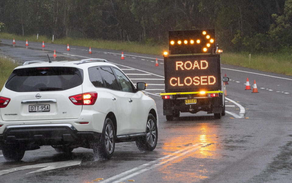 A vehicle is diverted as a road is closed due to flooding on the outskirts of Port Stephens, 200 kilometers (120 miles) north of Sydney, Australia, Sunday, March 21, 2021. Residents across the state of New South Wales have been warned to prepare for possible evacuations, as NSW Premier Gladys Berejiklian said the state's flood crisis would continue for several more days. (AP Photo/Mark Baker)