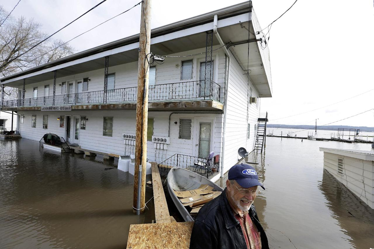Steve Peters, property manager of the Lakeview Apartments, which is surrounded by flood waters from the Illinois River, uses a make shift bridge to access dry land Wednesday, April 24, 2013, in Peoria Heights, Ill. The Illinois River finally crested Tuesday at 29.35 feet, eclipsing a 70-year record in Peoria. (AP Photo/Seth Perlman)