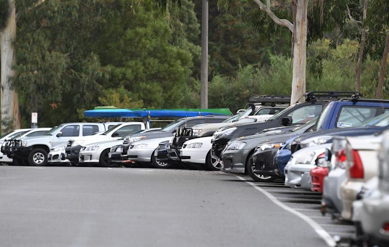 Dozens of cars fill up spaces in a car park.