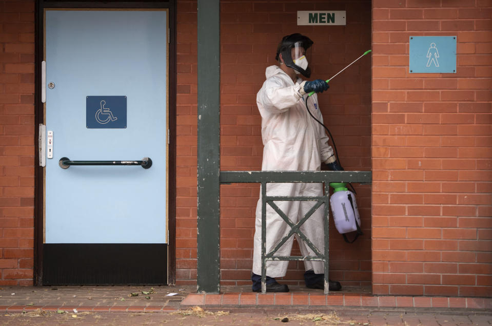 A man disinfects public toilets in Leicester, England, Monday June 29, 2020. The British government is reimposing lockdown restrictions in the central England city of Leicester after a spike in coronavirus infections, including the closure of shops that don't sell essential goods and schools. (Joe Giddens/PA via AP)