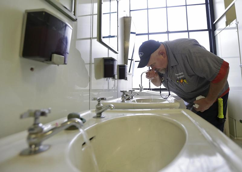 CORRECTS STATE TO W.VA. INSTEAD OF VA. - Al Jones of the West Virginia department of General Services tests the water as he flushes the faucet and opens a rest room on the first floor of the State Capitol in Charleston, W.Va., Monday, Jan. 13, 2014. Gov. Earl Tomblin announced that the water system is ready to be flushed by zones with safe drinking water after the chemical spill on Jan. 9. It could still be several days before everyone is cleared to use the water again, but officials were grateful to give the green light to about 6,000 to 10,000 customers. (AP Photo/Steve Helber)