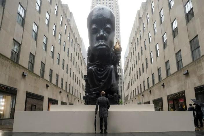 A man stands and looks at Sanford Biggers statue 'Oracle' in New York City