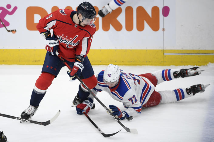 Washington Capitals defenseman Dmitry Orlov (9) battles for the puck against New York Rangers center Filip Chytil (72) during the second period of an NHL hockey game, Sunday, March 28, 2021, in Washington. (AP Photo/Nick Wass)