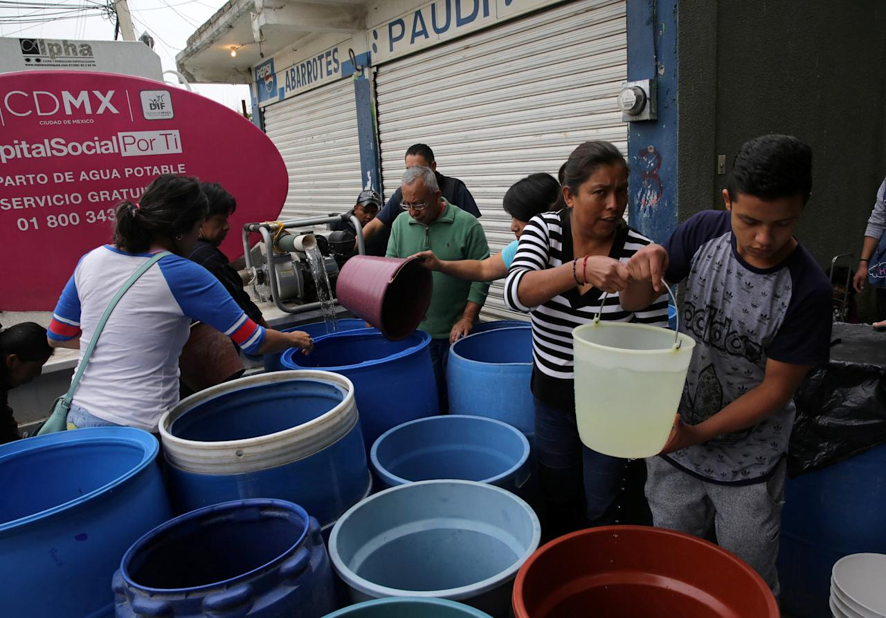 A worker fills tanks with water, after the earthquake on September 19, in San Juan Moyotepec neighbourhood in Mexico City, Mexico, October 18, 2017. REUTERS/Henry Romero