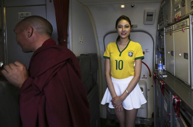 A flight attendant (R) wearing a Brazil soccer team jersey welcomes passengers onto an airplane travelling from Kunming to Hangzhou, in Kunming, Yunnan province June 23, 2014. A Chinese airline company renovated the cabin of one of its flights then dressed the flight attendants with soccer jerseys as a way to celebrate the 2014 Brazil World Cup and hoping to attract more customers, local media reported. REUTERS/Wong Campion (CHINA - Tags: SPORT SOCCER WORLD CUP SOCIETY TRANSPORT)
