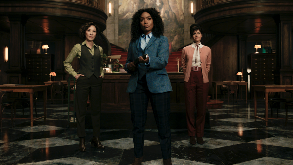 Michelle Yeoh, Angela Bassett, and Carla Gugino stand in a fancy room.