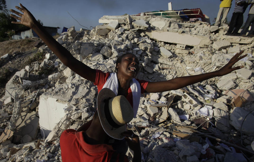 <p>Maxi Phalone sings praises to God after her sister was pulled alive from the rubble of a collapsed building in Port-au-Prince, Monday, Jan. 18, 2010. (Photo: Julie Jacobson/AP) </p>