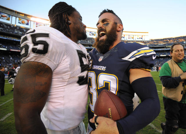 San Diego Chargers free safety Eric Weddle (32) laughs as he talks with Oakland Raiders outside linebacker Sio Moore (55) after of an NFL football game Sunday, Dec. 22, 2013, in San Diego. The Chargers won 26-13. (AP Photo/Denis Poroy)