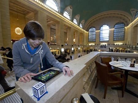 "Josh Rubinstein plays ""Alien Jailbreak"" on his iPad in Grand Central Station during American International Toy Fair in New York"