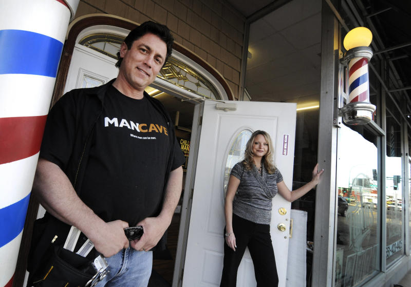In this March 9, 2012, photo Joel and Lisa Martin pose outside their barber shop and salon in Rosemount, Minn. The barber pole, one of the oldest signs that can be seen on storefronts across America, are an increasing source of friction between barbers and beauticians over which businesses get to display the iconic striped poles.  (AP Photo/Jim Mone)