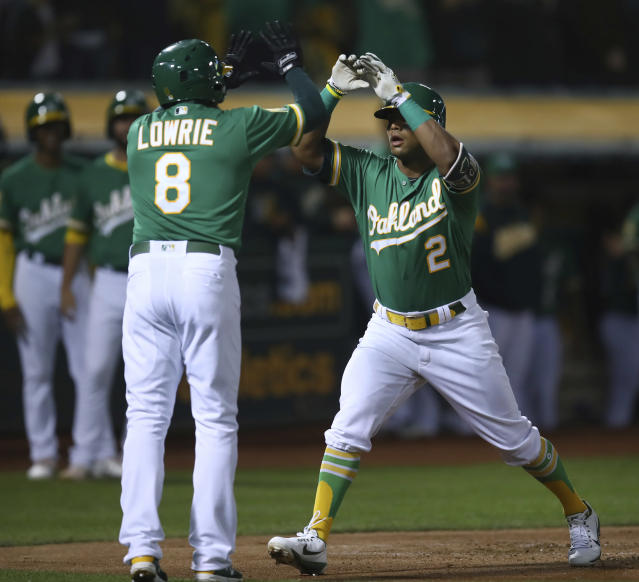 Oakland Athletics' Khris Davis, right, celebrates with Jed Lowrie (8) after hitting a two-run home run off Minnesota Twins' Jose Berrios during the first inning of a baseball game Friday, Sept. 21, 2018, in Oakland, Calif. (AP Photo/Ben Margot)