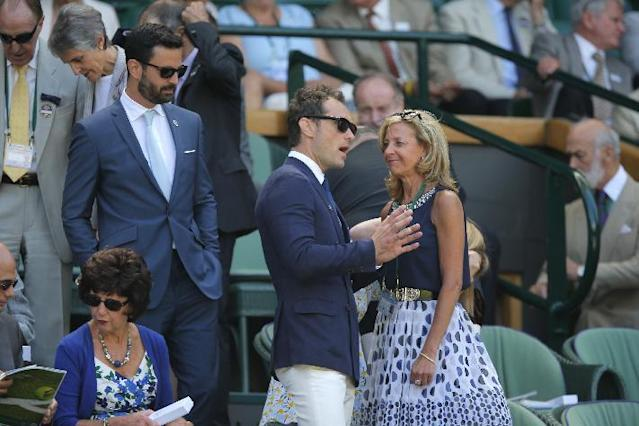 British actor Jude Law, center, arrives in the Royal Box on centre court prior to the men's singles semifinal match between Novak Djokovic of Serbia and Grigor Dimitrov of Bulgaria at the All England Lawn Tennis Championships in Wimbledon, London, Friday July 4, 2014. (AP Photo/Pavel Golovkin)