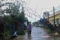 Man bikes past a broken sign as the Typhoon Molave lashes Vietnam's coast in Binh Chau village