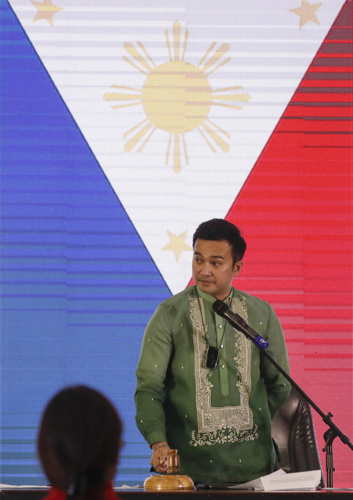 """Representative Lord Allan Velasco bangs the gavel after being sworn in as new house speaker by supporters at the Celebrity sports club in Quezon city, Philippines, Monday, Oct. 12, 2020. A large faction of Philippine legislators in the House of Representatives has elected a new leader but the incumbent speaker declared the vote """"a travesty"""" in a tense political standoff between two allies of the president. (AP Photo/Aaron Favila)"""