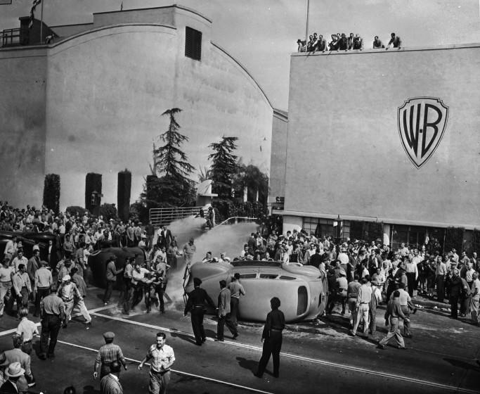 Oct. 5, 1945: Strikers outside of employee entrance to Warner Brothers Studios in Burbank. Strikers and non-strikers clashed in fights as non-strikers tried to cross picket line. Studio firemen, center, background, turn hose on battlers. Two workers' cars and officers' car, at the left, were overturned as they attempted to enter the studio. This photo appeared in the Oct. 6, 1945, Los Angeles Times.