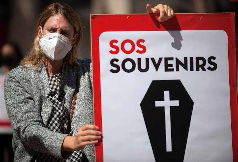 A protester wearing a mask holds a placard at Plaza de la Constitucion square during the demonstration in Malaga, Spain. Employees from S.O.S Souvenirs association who work in tourists souvenir stores, demand that the Spanish government ensures the survival of this industry. Photo: Jesus Merida/SOPA/LightRocket via Getty