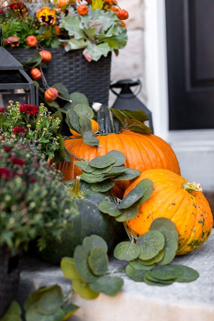 """<p>Use decorative greenery, like eucalyptus leaves, to fill any negative space between plantings, pumpkins, and other front porch decor. </p><p><a class=""""link rapid-noclick-resp"""" href=""""https://www.craftberrybush.com/2019/09/fall-front-porch-2019.html"""" rel=""""nofollow noopener"""" target=""""_blank"""" data-ylk=""""slk:GET THE TUTORIAL"""">GET THE TUTORIAL</a></p>"""