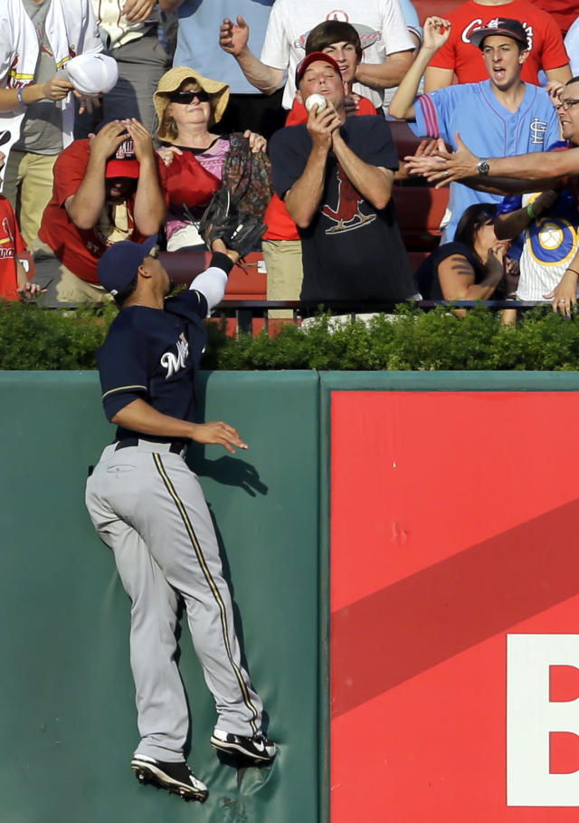 Milwaukee Brewers center fielder Carlos Gomez climbs the outfield wall as a fan catches a solo home run by St. Louis Cardinals' Kolten Wong during the first inning of a baseball game Saturday, Aug. 2, 2014, in St. Louis. (AP Photo/Jeff Roberson)