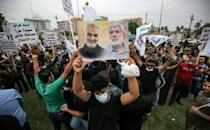 A protester holds aloft portraits of (L to R) Iranian commander Qasem Soleimani and Iraqi paramilitary commander Abu Mahdi Al-Muhandis, both killed in a US drone strike in January