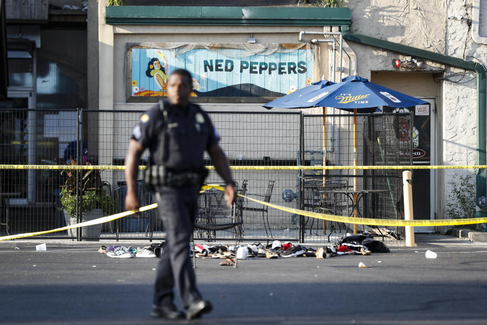 Shoes are piled outside the scene of a mass shooting including Ned Peppers bar, Sunday, Aug. 4, 2019, in Dayton, Ohio. Several people in Ohio have been killed in the second mass shooting in the U.S. in less than 24 hours, and the suspected shooter is also deceased, police said. (AP Photo/John Minchillo)