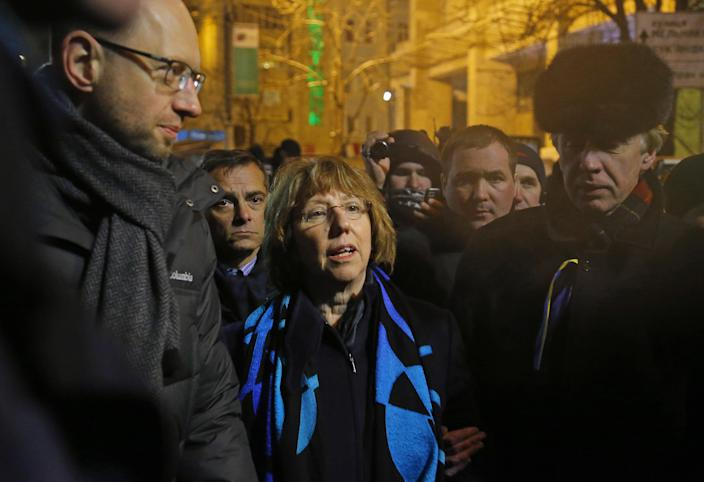 Ukrainian opposition leader Arseniy Yatsenyuk, left, and EU foreign policy chief Catherine Ashton, center, arrive to meet Pro-European Union activists gathered on the Independence Square in Kiev, Ukraine, Tuesday, Dec. 10, 2013. Some demonstrators arrested in the massive protests sweeping Ukraine's capital will be released, embattled President Viktor Yanukovych promised Tuesday, trying to defuse a political standoff that is threatening his leadership. (AP Photo/Sergei Grits)