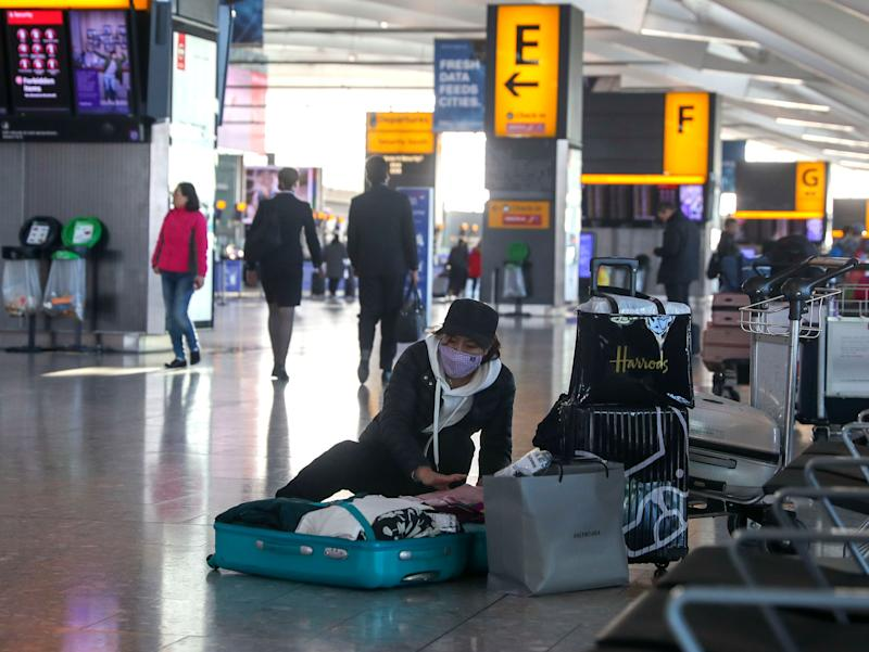 A woman wearing a face mask packs her suitcase in the departures area of Terminal 5 at Heathrow Airport, after it was announced British Airways had suspended all services to and from China. (Photo: PA)