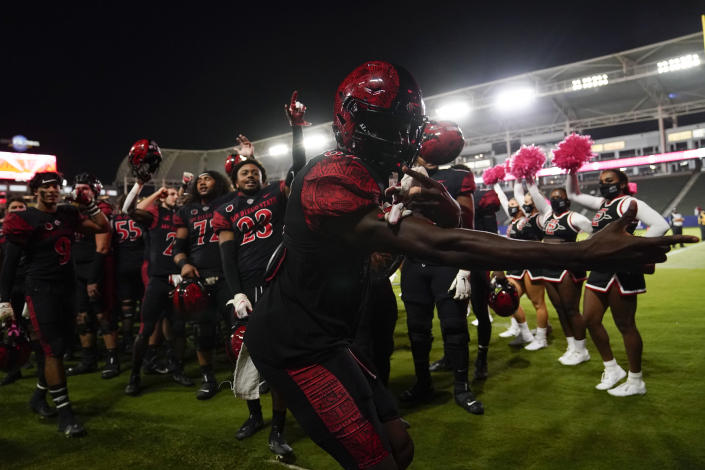 San Diego State players celebrate a 31-7 win over New Mexico after their NCAA college football game Saturday, Oct. 9, 2021, in Carson, Calif. (AP Photo/Ashley Landis)
