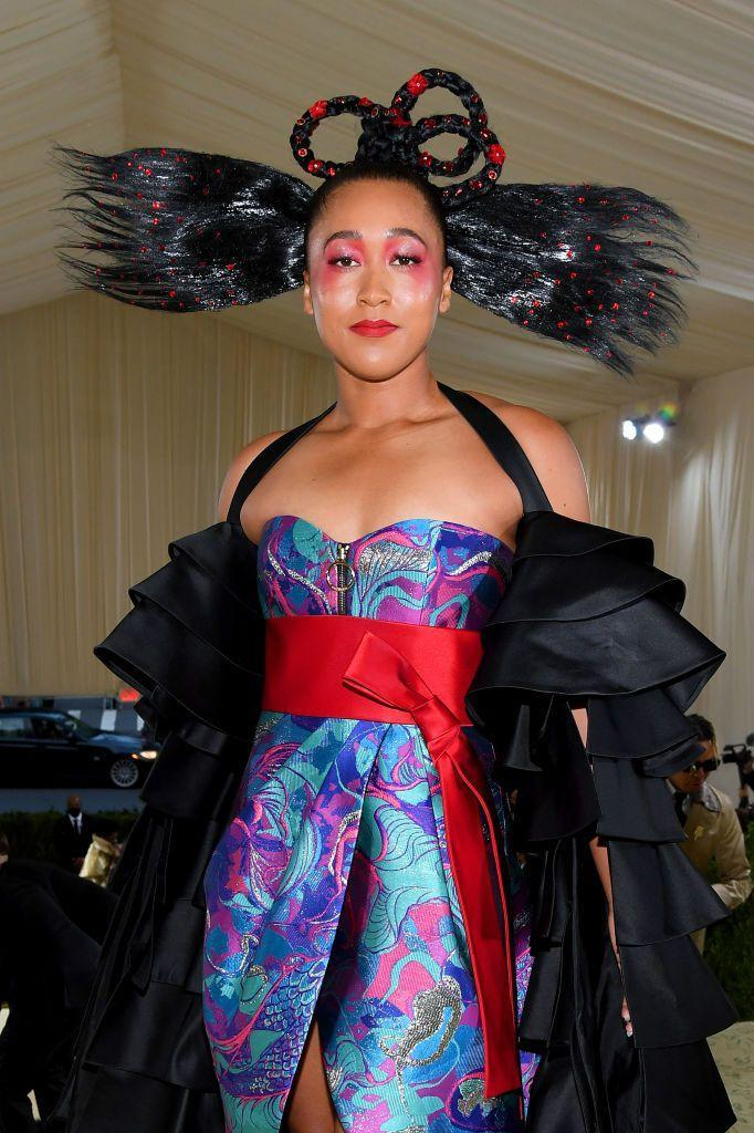 <p>The tennis star appeared in a fiery look with fleshed-out eyeshadow that connected to her dazzling highlighter, and a fire engine red lip to boot. Atop her head were intricate braids morphed into a pretzel-like design and stiff strands sticking out at the sides.</p>