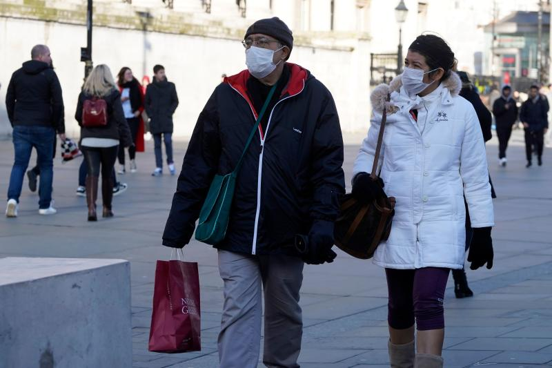 Pedestrians wear surgical masks as they shop in central London.