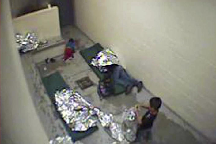 FILE - This Sept. 2015, file image made from U.S. Border Patrol surveillance video shows a child crawling on the concrete floor near the bathroom area of a holding cell, and a woman and children wrapped in Mylar sheets at a U.S. Customs and Border Protection station in Douglas, Ariz. A years-old lawsuit challenging detention conditions in several of the Border Patrol's Arizona stations will go to trial Monday, Jan. 13, 2020, as the agency as a whole has come under fire following several migrant deaths. The lawsuit was first filed in June 2015 and applies to eight Border Patrol facilities in Arizona where attorneys say migrants are held in unsafe and inhumane conditions. (U.S. Border Patrol via AP, File)
