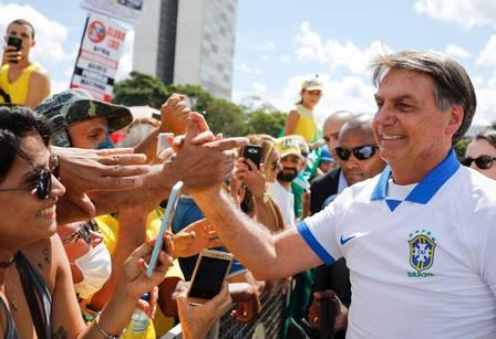 87515038_Brazilian-President-Jair-Bolsonaro-greets-supporters-in-front-of-th