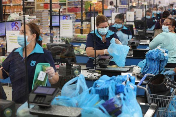 PHOTO: Cashiers stands behind a partial protective plastic screen and wear a mask and gloves as they work at the Presidente Supermarket on April 13, 2020, in Miami. (Joe Raedle/Getty Images)