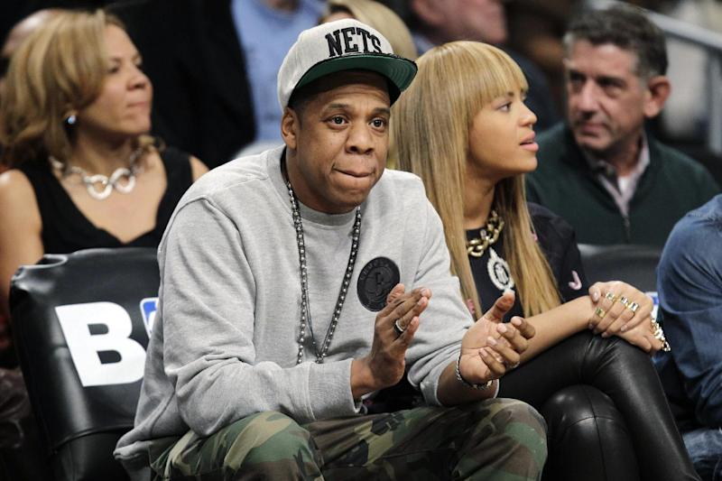 FILE - In this Nov. 26, 2012, file photo, rap mogul and Brooklyn Nets minority owner Jay-Z and his wife, Beyonce, watch an NBA basketball game between the Nets and the New York Knicks at Barclays Center in New York. Jay -Z is selling his stake in the Nets so he can become certified as a player agent, possibly before the end of the season. The process is underway, with paperwork already filed, a person with knowledge of the details said Wednesday, April 10, 2013. NBA rules prevent anyone from being involved in ownership and player representation. (AP Photo/Kathy Willens, File)