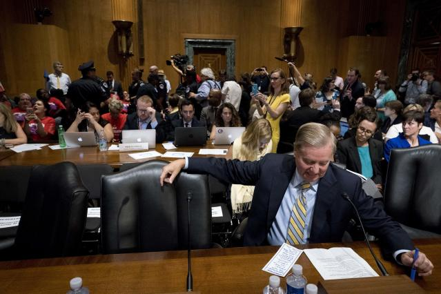 <p>Sen. Lindsey Graham, R-S.C. waits protesters are removed after disrupting a Senate Finance Committee hearing to consider the Graham-Cassidy healthcare proposal, on Capitol Hill, Monday, Sept. 25, 2017, in Washington. (AP Photo/Andrew Harnik) </p>
