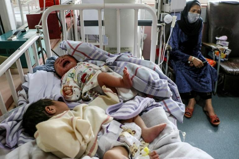 A woman sits next to newborn babies who lost their mothers following an attack on a Kabul maternity hospital (AFP Photo/STR)