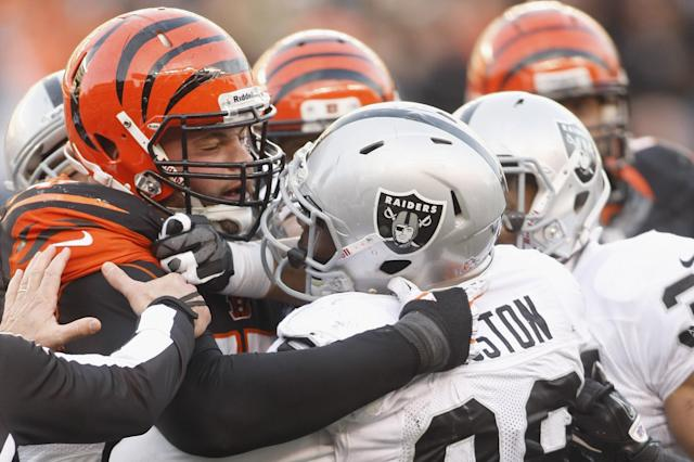 CINCINNATI, OH - NOVEMBER 25: Andrew Whitworth #77 of the Cincinnati Bengals fights with Lamaar Houston #99 of the Oakland Raiders during their game at Paul Brown Stadium on November 25, 2012 in Cincinnati, Ohio. The Bengals defeated the Raiders 34-10. (Photo by John Grieshop/Getty Images)